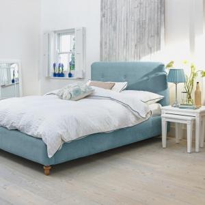 Niebieska tkanina łóżka nada wnętrzu sypialni świeży styl. Fot. Agros