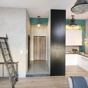 Ścianka działowa z szafą wnękową oddziela wąską kuchnię od reszty pomieszczenia. Projekt: Małgorzata Chabzda. Fot. Bartosz Jarosz