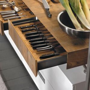 Drewniany blat i szuflady podblatowe efektownie kontrastują z białymi frontami. Fot. Marchi