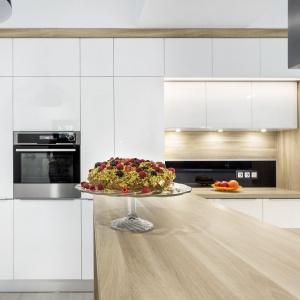 Meble kuchenne Salt & Pepper marki A&K Kuchnie. Fronty MDF lakier połysk, ramy i blat z laminatu drewnopodobnego, uchwyty krawędziowe ze stali szczotkowanej, na ścianie czarny lacobel połączony z laminatem drewnopodobnym, oświetlenie ledowe, cokoły przypodłogowe aluminiowe, okap wyspowy marki Faber. Fot. A&K Kuchnie