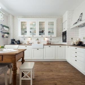 Meble kuchenne Provence marki A&K Kuchnie. Fronty lite drewno dębowe, lakierowane na biało, blaty z laminatu drewnopodobnego, uchwyty w kolorze starego złota, w witrynach przeźroczyste szkło fazowane, oświetlenie punktowe ledowe, obudowa piekarnika i okapu wykonana z karton-gipsu, wszystkie zawiasy i prowadnice marki Blum. Fot. A&K Kuchnie