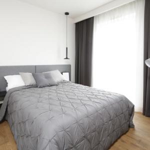 Proste, szare panele na ścianie za łóżkiem podkreślają minimalistyczny wystrój sypialni. Projekt: Katarzyna Uszok-Adamczyk. Fot. Bartosz Jarosz