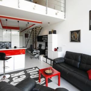 Czarna, skórzana sofa to rozwiązanie, które sprawdzi się w każdym wnętrzu. czerwone dodatki dodają sofie ciekawy wygląd. Projekt: Monika Olejnik Fot. Bartosz Jarosz
