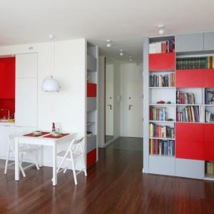 Czerwone wstawki w meblach dobrze komponują się z bielą. Projekt Iza Szewc. Fot. Bartosz Jarosz