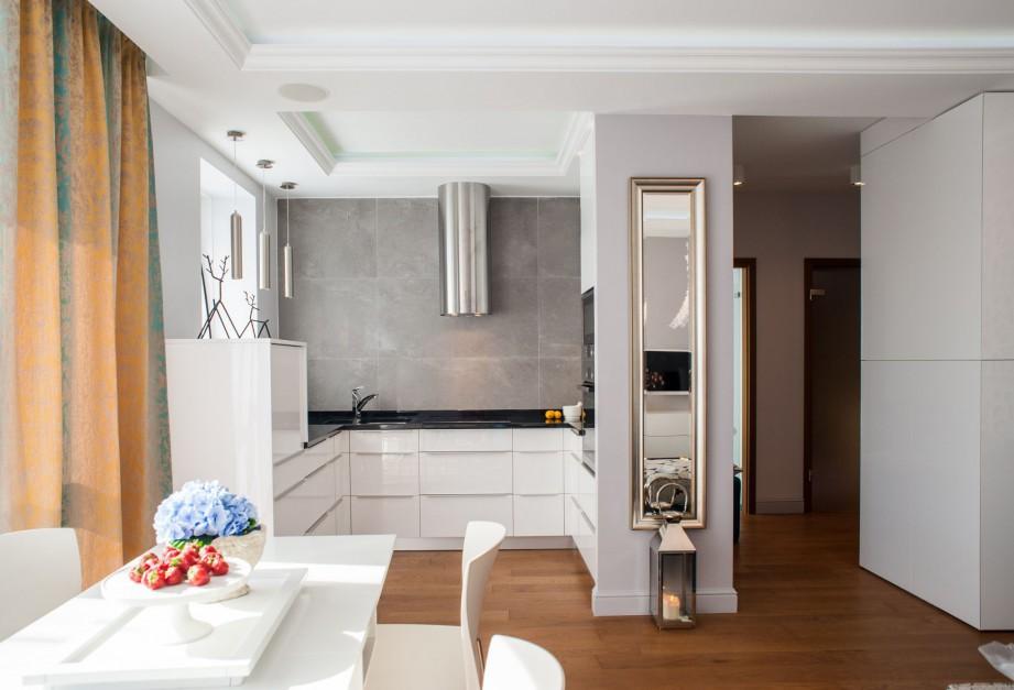 Biała kuchnia w połysku,  kształcie litery U. Stanowi doskonałe tło dla aranżacji salonu. Projekt: Arkadiusz Grzędzicki. Fot. Bartosz Jarosz