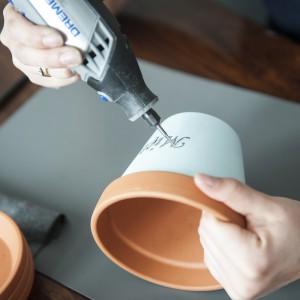 Używając urządzenia Dremel 3000 oraz końcówki do frezowania 9910, literka po literce robimy na napisie małe wgłębienia tak, żeby pojawiła się ceglasta barwa doniczki. Fot. Dremel