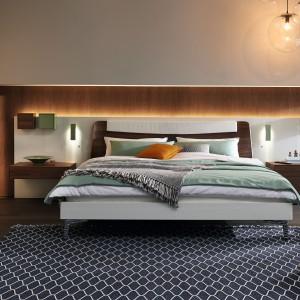 Łóżko firmy Hülsta połączone z panelem ściennym zawierającym półki, stoliki nocne i oświetlenie. Fot. Hülsta