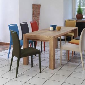 Jadalnia z kolorowymi krzesłami przy stole z litego drewna. Fot. Klose