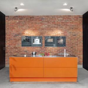 Ciemne drewno zabudowy dobrze komponuje się z cegłą na ścianie i pomarańczową wyspą. Fot. Zajc Kuchnie