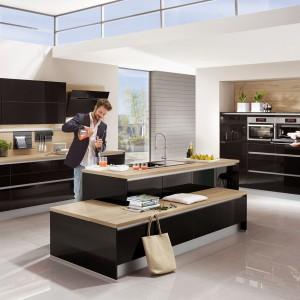 Drewniany blat doskonale podkreśla nowoczesny styl czarnych połyskujących frontów. Fot. Nobilia