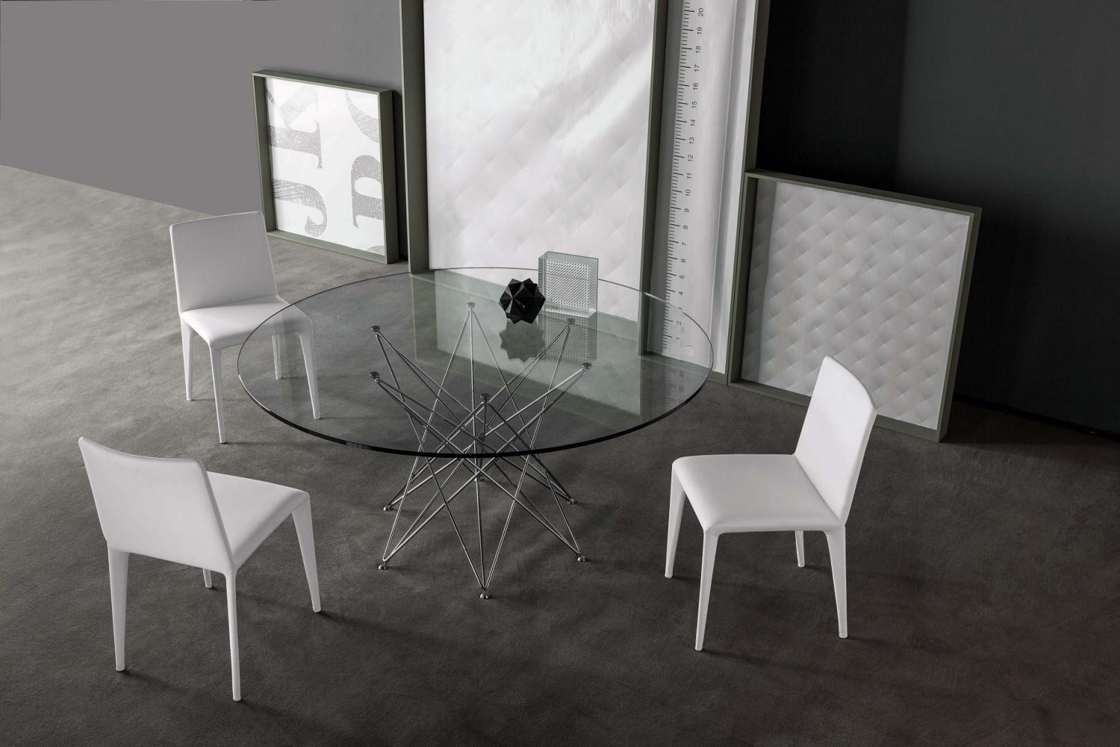 Okrągły  stół ze szklanym blatem zamiast nóg ma delikatna pajęczynę wykonaną ze stalowych prętów. Fot. Bonaldo