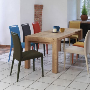 Do prostego drewnianego stołu pasują kolorowe tapicerowane krzesła. Fot. Klose