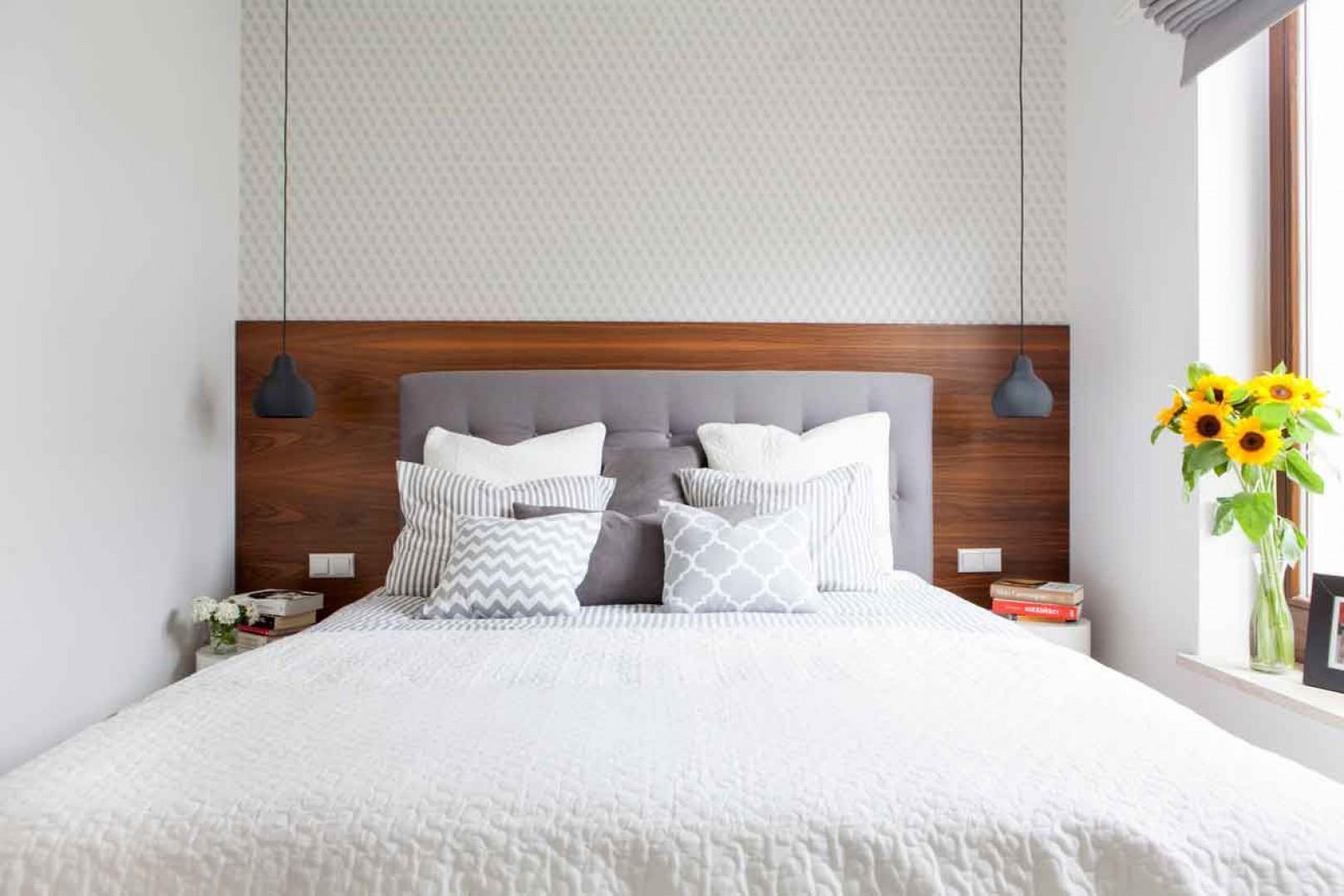 Przytulny nastrój  w tej sypialni tworzy drewno orzecha o ciepłej barwie, którym wyłożono ścianę za łóżkiem, a także miękkie tekstylia - tapicerowany zagłówek łóżka i leżące na nim poduszki. Fot. MGN