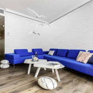Błękitna sofa w połączeniu z drewnianą podłogą i białymi ścianami podkreśla marynistyczny klimat salonu. Projekt Paulina Kasprowicz