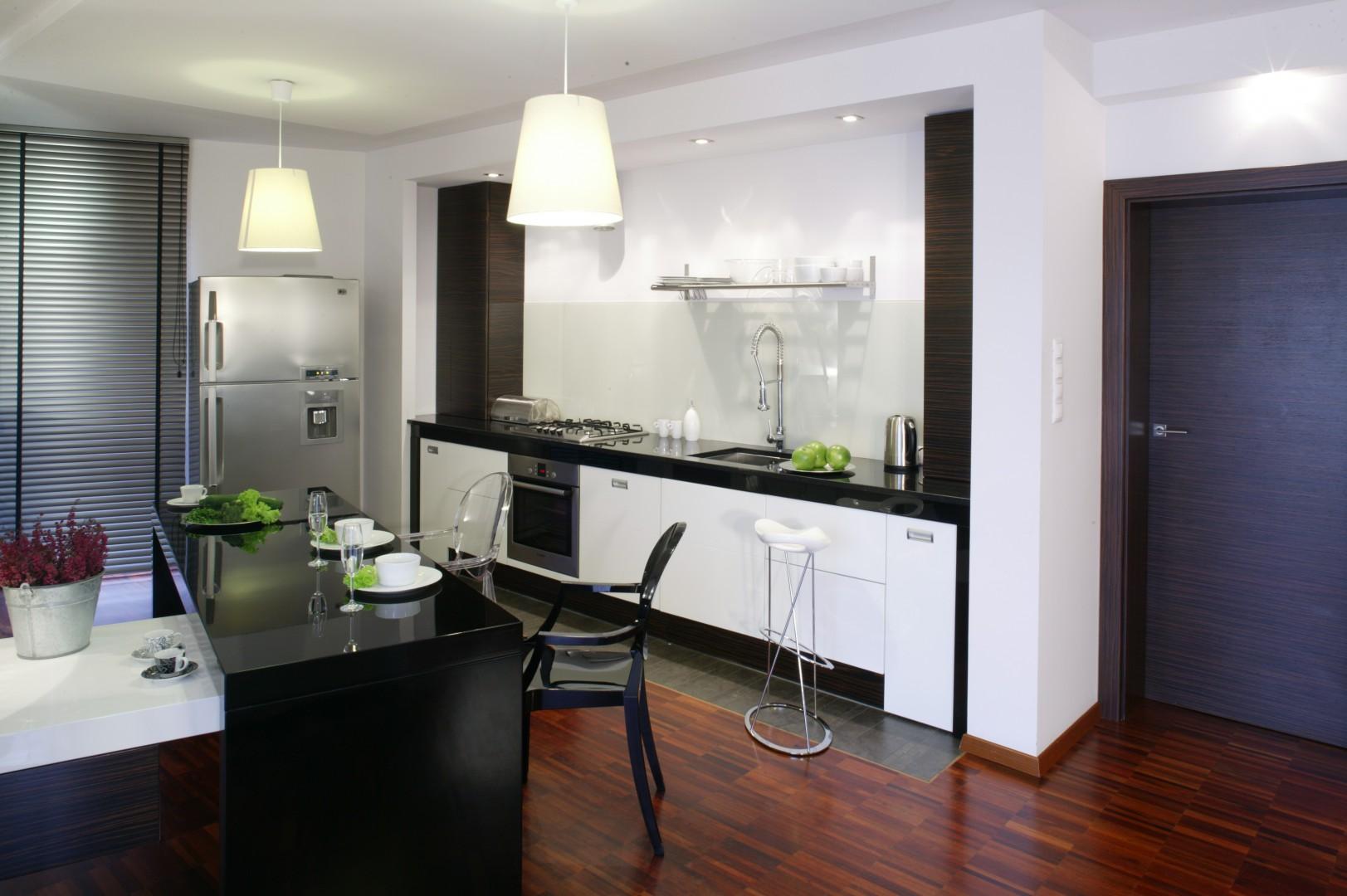 Czarna kuchenna wyspa doskonale prezentuje się w towarzystwie bieli. Projekt Karolina Pawłowicz. Fot. Bartosz Jarosz