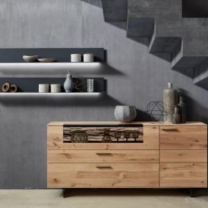 Z drewnianymi frontami komody dobrze komponują się szare, wiszące półki. Fot. Salony Agata