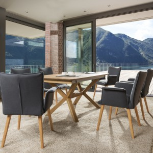 Do drewnianego stołu pasują krzesła w szarej tapicerce. Fot. Klose