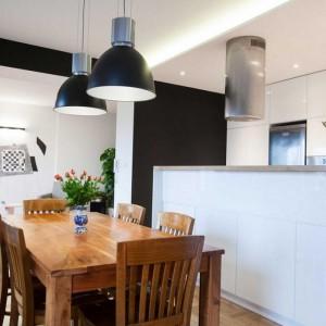 Ścianka skutecznie zasłania kuchnię z neutralną, nierzucającą się w oczy zabudową. Zwieńczający ją drewniany blat tworzy półkę, na której można postawić niemieszczące się na stojącym obok stole napoje i potrawy albo kwiaty czy inne dekoracyjne przedmioty. Fot. Pracownia Architektoniczna MGN