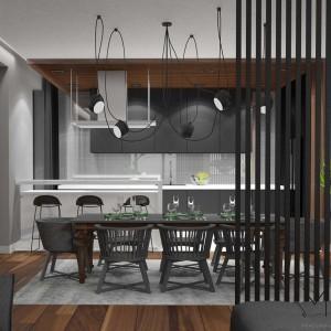 W sporej przestrzeni dziennej strefę kuchenno-jadalną od części wypoczynkowej oddziela przesłona z drewnianych listew, zbudowana na około jednej trzeciej długości pomieszczenia. Fot. Pracownia Architektoniczna MGN