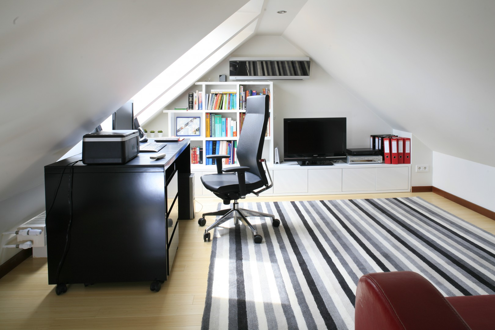 Miejsce pod skosami idealnie nadaje się na ustawienie biurka i wygodnego fotela. Projekt Aleksandra Wołczyk. Fot. Bartosz Jarosz