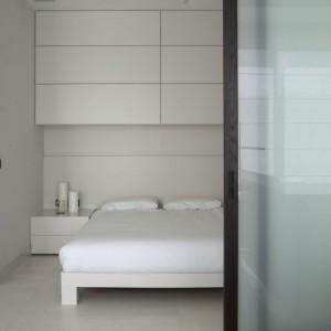 Dzięki drzwiom przesuwnym skomponowano ruchomą ścianę, która oddziela minimalistyczną, surową sypialnię od części dziennej mieszkania. Fot. Studio O.