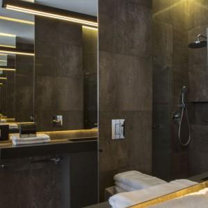 Lampa nad umywalką w łazience - brązowa kreska skonstruowana przez pracownię stolarską według projektu Studio.O. Fot. Studio O.