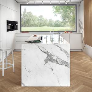 Biel wysokich i niskich szafek przełamuje wyspa kuchenna, przypominająca monolityczny blok kamienia. Produkcja: Zajc. Projekt: Moo Moo. Fot. Tom Kurek