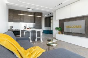 Uniwersalny minimalizm, drewno i biel w apartamencie na wynajem