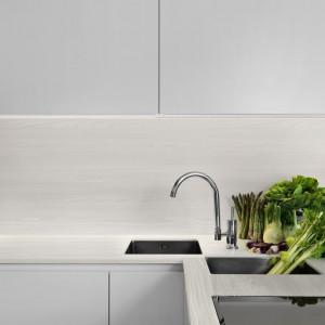 Ciekawym i bardzo oryginalnym sposobem na zaaranżowanie powierzchni roboczej w kuchni, jest zastosowanie tego samego materiału na blacie, jak i na ścianie tuż nad nim. Fot. Pfleiderer
