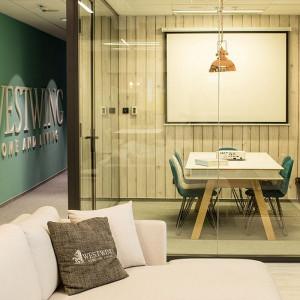 Już od wejścia pracowników i odwiedzających firmę gości zapraszają przeszklone, tematyczne salki spotkań. Fot. Westwing Home & Living