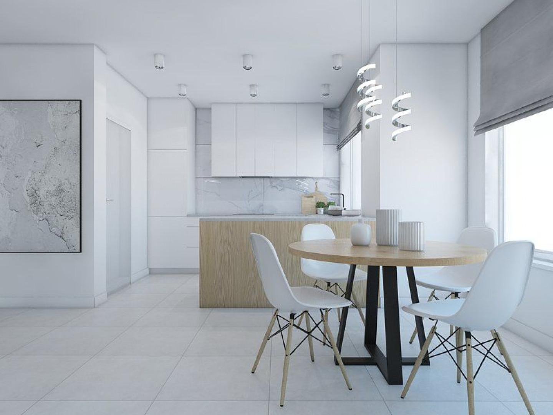 Ścianę w tej kuchni zabezpieczono wielkoformatowymi płytkami ceramicznymi do złudzenia przypominającymi pięknie żyłkowany marmur. Taka okładzina nie tylko dobrze chroni ścianę, ale i jest dużą ozdobą nowoczesnego wnętrza. Fot. Pracownia Projektowa MGN