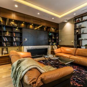 Za regałem zaczyna się część wypoczynkowa z kominkiem i dużą biblioteką oraz wygodnymi skórzanymi sofami. Fot. Viva Design