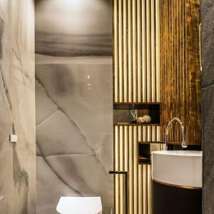 W gościnnej łazience podświetlana, ażurowa ściana została wykonana przez stolarza, zaś podłogi i ściany wyłożono kamienną okładziną, a na ich tle ustawiono wolno stojącą umywalkę obłożoną naturalną skórą. Fot. Viva Design