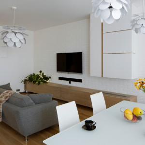 Na tle jasnych ścian w salonie stanęła szara sofa marki Loop&Co. Nie tylko wpisuje się w najnowsze trendy, ale jest też wygodnym meblem do odpoczynku przy strefie tv. Projekt: Inter-Arch Architekci. Fot. Inter-Arch Architekci