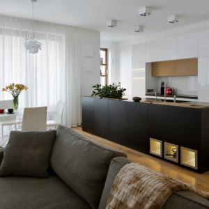Przedłużenie kuchni stanowi przykuwająca wzrok wyspa kuchenna w ciemnej kolorystyce, mieszcząca płytę grzejną, zlew i blat roboczy. Projekt: Inter-Arch Architekci. Fot. Inter-Arch Architekci
