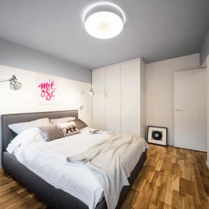 W sypialni dominują biel i ciepły odcień szarości, które idealnie komponują się z drewnianą podłogą. Projekt: 3XEL Architekci. Fot. Paweł Augustyniak