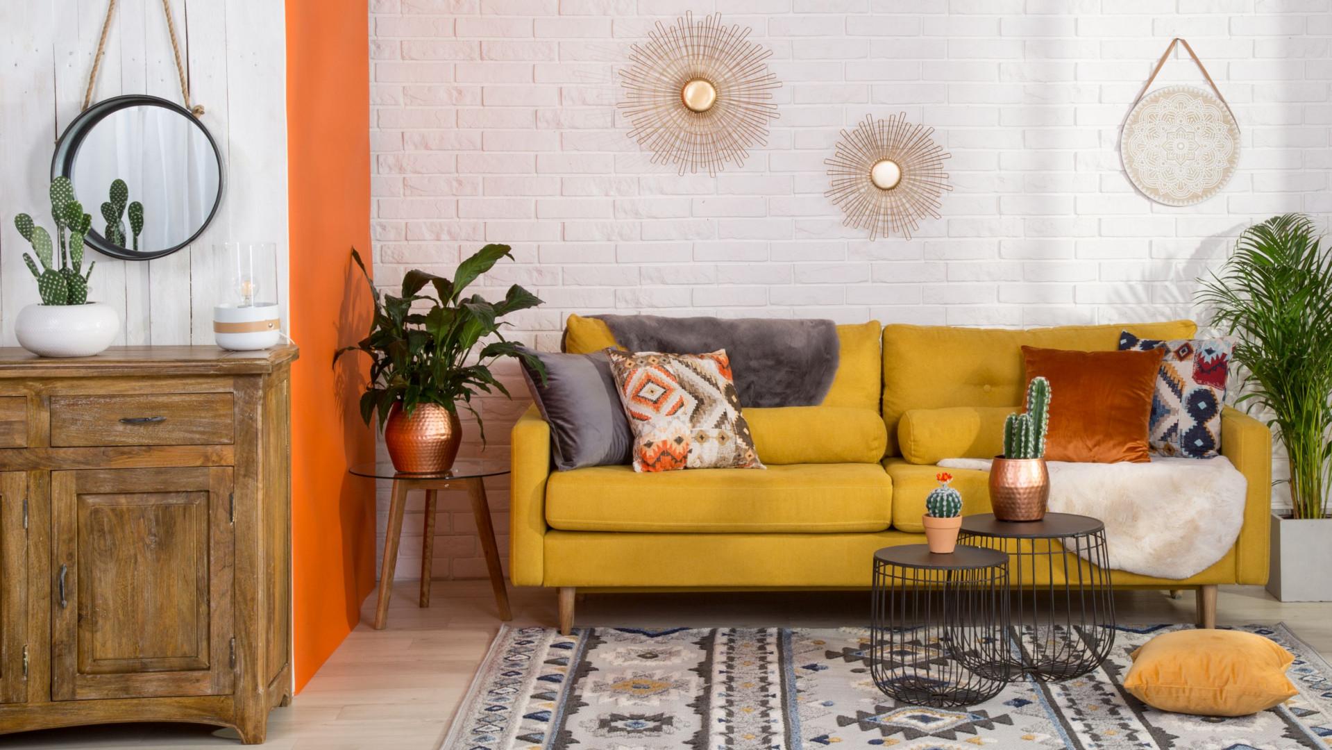Sofa w kolorze ciepłej żółci dobrze wygląda na tle stonowanych kolorów. Fot. Salony Agata