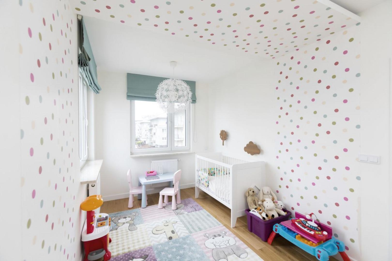 Otulająca wnętrza tapeta w kolorowe groszki, dywan w rozkoszne zwierzaki i dużo miejsca do zabawy – pokój jest tak radosny, że trzylatce nie chce się z niego wychodzić. Projekt: Małgorzata Górska-Niwińska (Pracownia Architektoniczna MGN).
