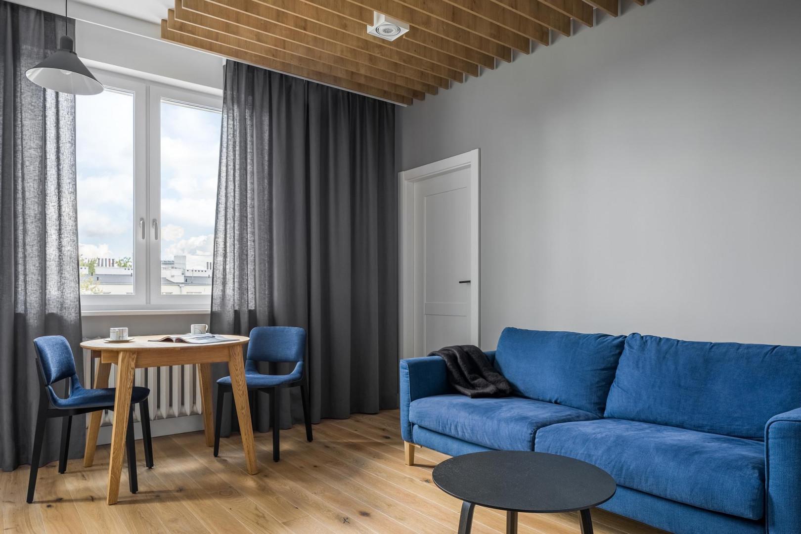Motywem przewodnim są odcienie niebieskiego, które występują w lakierowanych meblach oraz w tapicerce sofy i krzeseł. Projekt: 3XEL Architekci. Fot. Dariusz Jarząbek