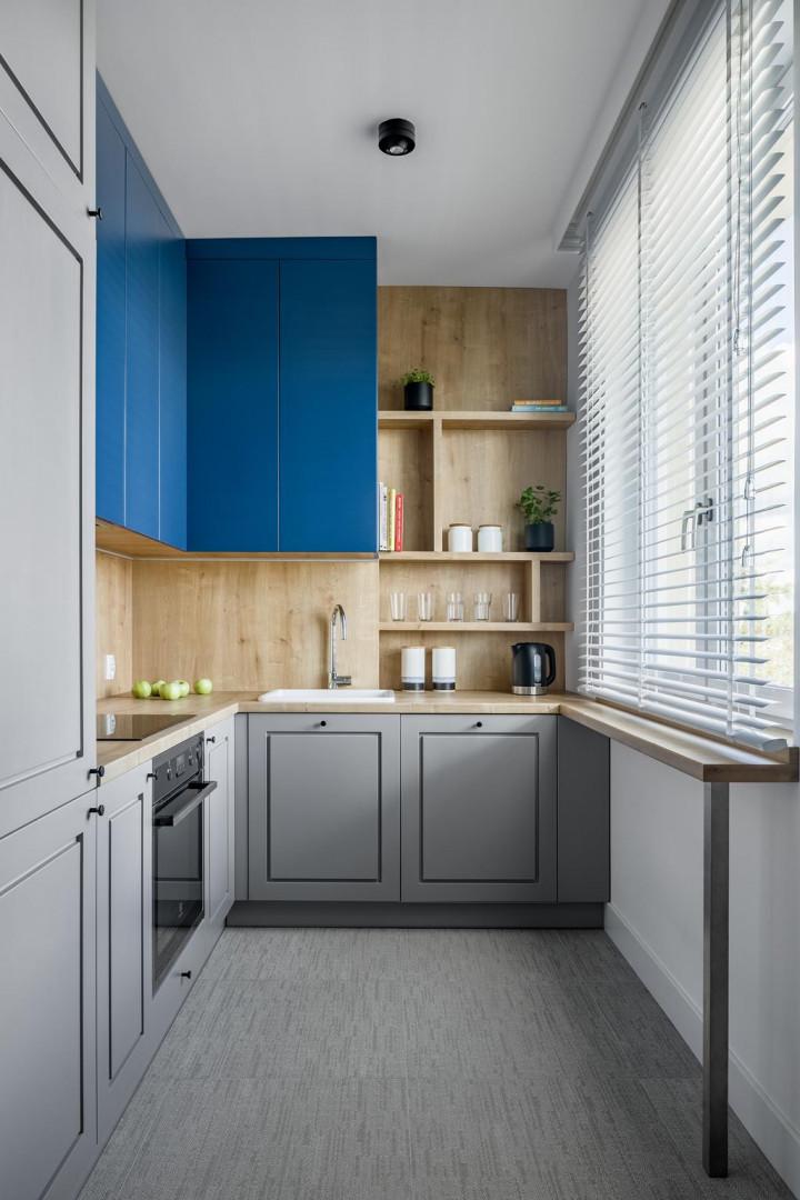 Architekci nie chcieli, żeby kuchnia wydawała się ciężka, dlatego na osi widocznej z salonu postawili na otwarte półki, na których można wyeksponować rośliny czy inne dodatki. Projekt: 3XEL Architekci. Fot. Dariusz Jarząbek