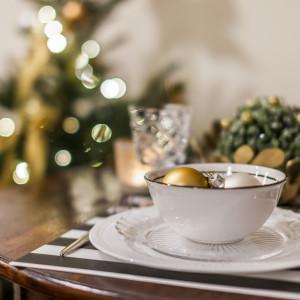 W przypadku jadalni niezwykle ważne jest odpowiednie nakrycie stołu. Możemy wykorzystać do tego białą porcelanę ze złotymi zdobieniami. Świąteczną kompozycję zbudują subtelne stroiki, serwetki i przybrania zastawy stołowej w kolorze złota i zieleni . Fot. Pracownia Kodo