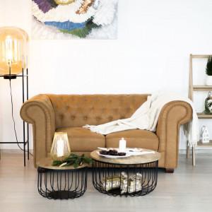 Sofa typu chesterfield zestawiona z kawowymi stolikami z drewna dobrze sprawdzi się w typowo domowym salonie. Fot. Make Home