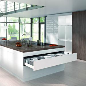 Projektanci nowoczesnych wnętrz kuchennych dążą do te-go, aby zabudowa meblowa stanowiła jednorodną całość, chęt-nie więc wprowadzają duże płaszczyzny drzwi przesuwnych, którymi zastępują zlepek mniej-szych modułów szafkowych. Fot. Hettich