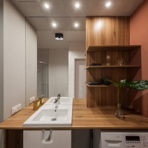 W kuchni na uwagę zasługują nie tylko drewniane fronty szafek, ale także betonowe wykończenie blatów czy satynowa powierzchnia ścian. Projekt: pracownia Kodo. Fot. Pracownia Kodo