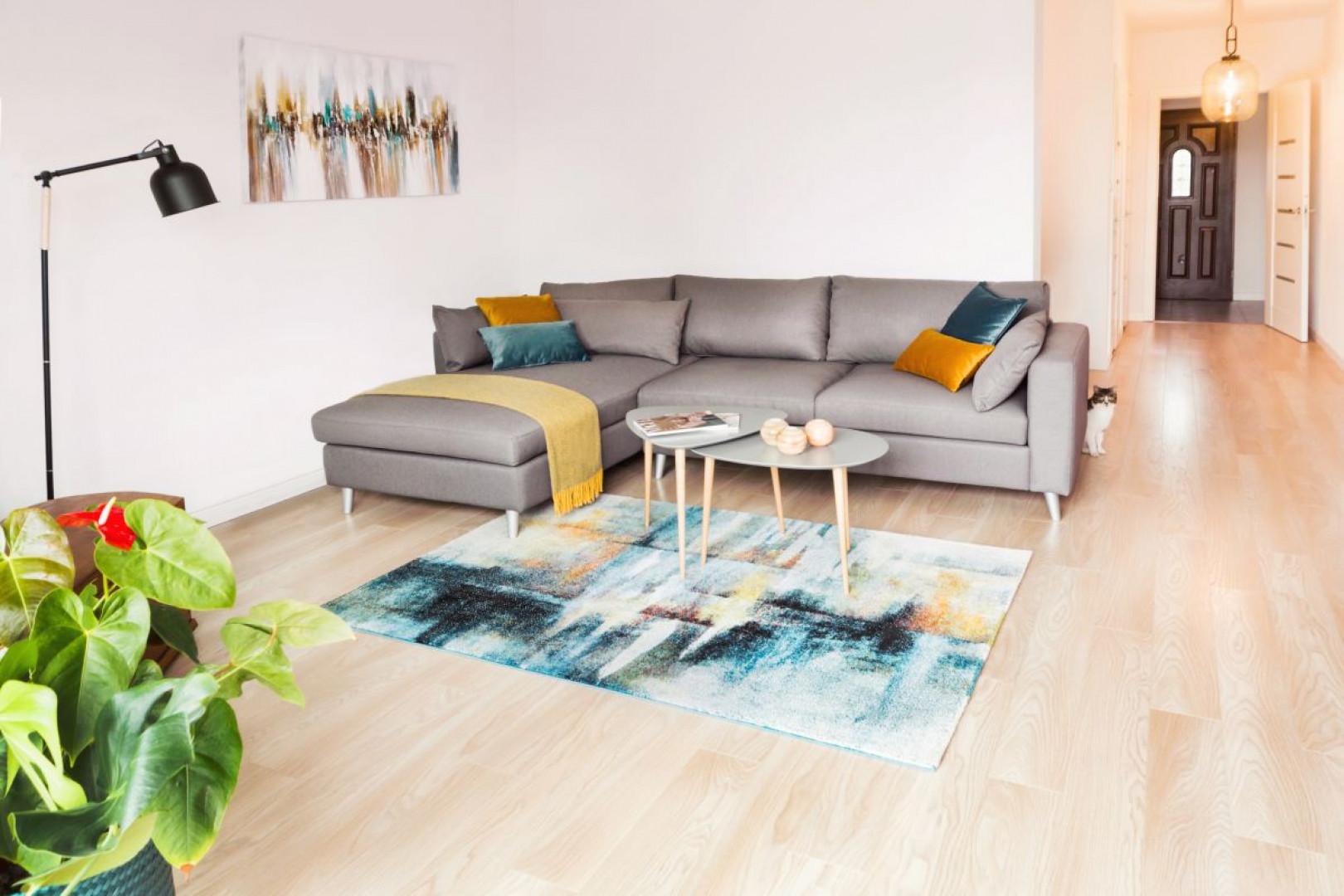 Centralnym punktem salonu jest wygodny i funkcjonalny narożnik, utrzymany w neutralnym, szarym kolorze. Projekt: Kinga Świątek-Wolna. Fot,. Make Home