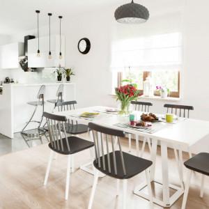 W jadalni do dużego białego stołu dopasowano bukowe krzesła-patyczaki na białych nogach z czarno-szarym siedziskiem i oparciem. Projekt: Kinga Świątek-Wolna. Fot,. Make Home
