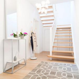 W korytarzu znalazła się stylowa konsolka. To bardzo elegancki i praktyczny mebel, a jego ażurowa konstrukcja sprawia, że nie przytłacza pomieszczenia. Projekt: Kinga Świątek-Wolna. Fot,. Make Home