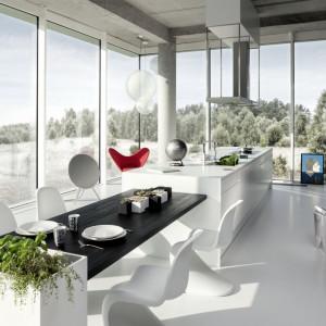 Stół zintegrowany z wyspą kuchenną wyznacza umowną granicę między otwartą kuchnią a salonem. Fot. Zajc