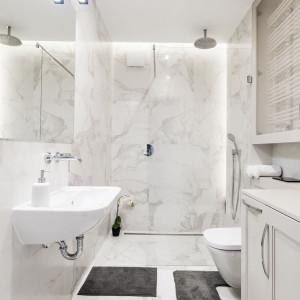 Imitacje kamieni są coraz doskonalsze! Dowodem na to są płytki polerowanego gresu, którymi wykończono ściany i podłogę tej łazienki. Nawet gdy patrzy się na nie z bliska, odnosi się wrażenie, że to naturalny marmur. Projekt: Małgorzata Górska-Niwińska. Fot. Pracownia Architektoniczna MGN