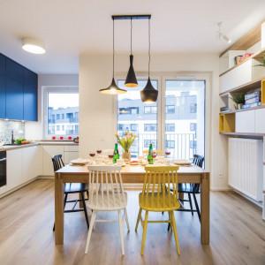 W kuchni kolorowe krzesła i barwne fronty górnych szafek wyróżniają się na tle jasnej zabudowy i drewnianych blatów. Fot. Kodo